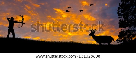 Silhouette of a bow hunter aiming at a White tail buck against an evening sunset. - stock photo