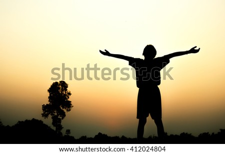 Silhouette of a boy exercising over beautiful sunset background.