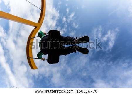 Silhouette of a boy on a swing against a deep blue sky with puffy clouds - stock photo