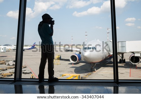 silhouette of a boy photographing a plane through the window of Airport - stock photo