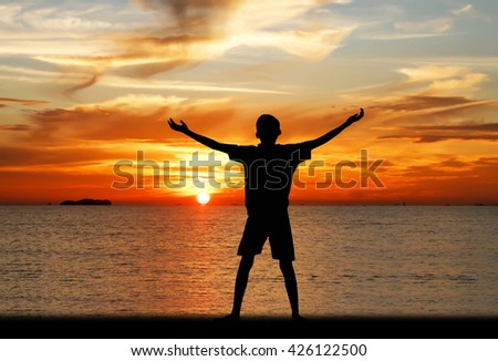 Silhouette of a boy with hands raised on a beach at the sunset concept for religion, worship, prayer and praise. - stock photo