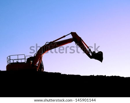 Silhouette of a bulldozer on a ridge with blue mauve sky background - stock photo