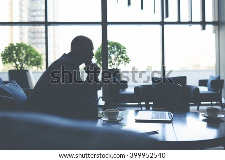 Silhouette of a businessman is thinking about future conversations with investors, while is sitting in cafe with net-book. Male financier is watching financial news in internet via laptop computer - stock photo