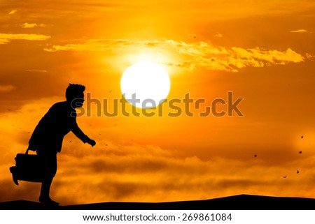 silhouette of a businessman with lab-top running with sun rise. - stock photo