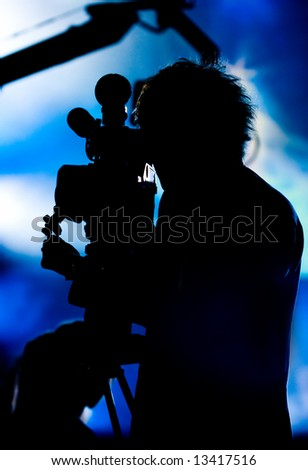 Silhouette of a cameraman filming fashion show catwalk - stock photo