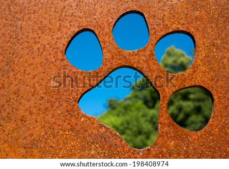 Silhouette of a cat paw in rusty metal wall in front of trees - stock photo