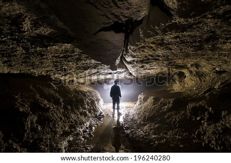 silhouette of a cave explorer in the underground - stock photo