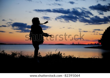 Silhouette of a child girl with braids playing in the sunset - stock photo