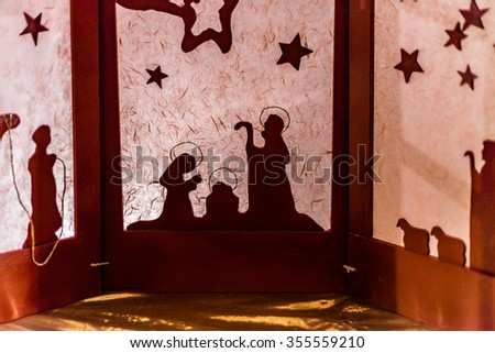silhouette of a Christmas Nativity scene, the Blessed Virgin Mary and Saint Joseph watch over the Holy Child Jesus - stock photo