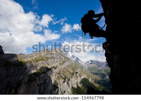 Silhouette of a climber above mountain peaks - stock photo