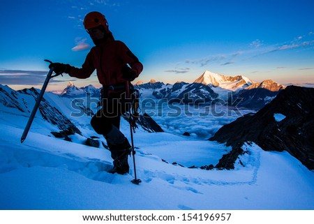 Silhouette of a climber on a glacier with high peaks in the background