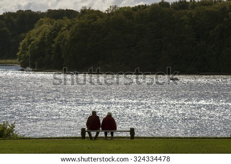 Silhouette of a couple enjoying the afternoon on a calm and peaceful relaxing spot close to the sea. - stock photo