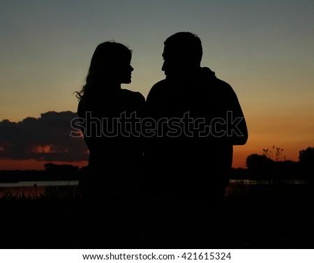 silhouette of a couple in love at sunset - stock photo