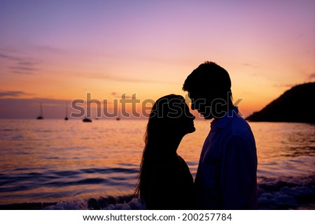Silhouette of a couple in love on a sunset tropical background. - stock photo