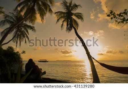 Silhouette of a couple/ Lover looking at sunset in Maldive. Natural light and dark. Couple Vacation, back-light of a couple silhouette breathing deep fresh air at warm sunrise in front of sun