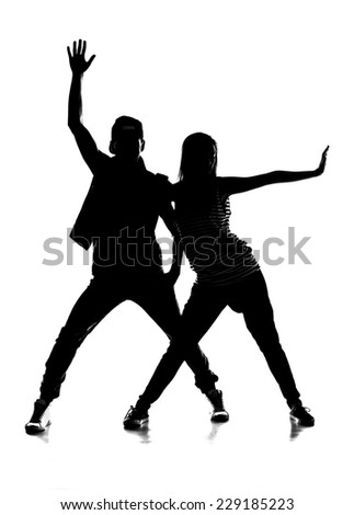 Silhouette of a couple of young man and woman dancing hip-hop at studio.