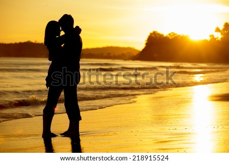 Silhouette of a couple on the beach at sunset - stock photo
