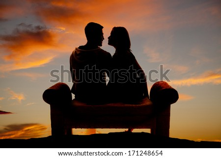 Silhouette of a couple sitting on a bench, outdoors. - stock photo