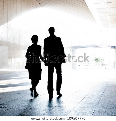 Silhouette of a couple walking on a light background.  Blurred motion.