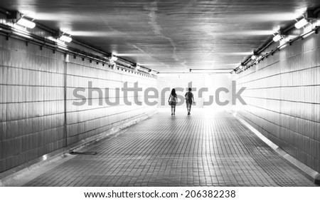Silhouette of a couple walking together in the tunnel - stock photo