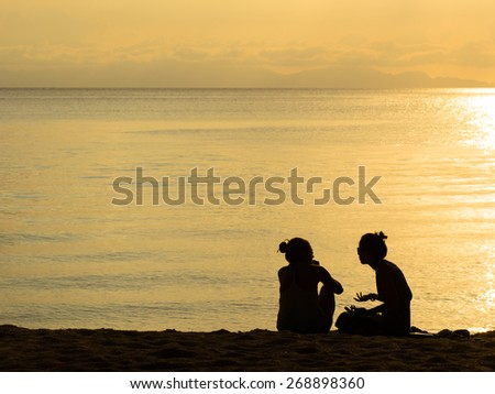 Silhouette of a couple woman sitting and talking together on the beach, Lipe island, Thailand. - stock photo