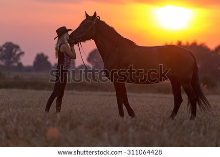 Silhouette of a cowgirl and horse. - stock photo