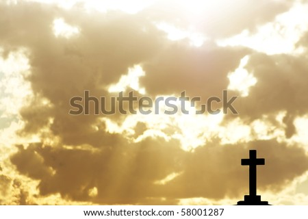 Silhouette of a cross in beams of light - stock photo