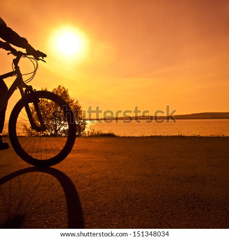 silhouette of a cyclist at  orange or yellow sunset With shadow Copy space for inscription - stock photo