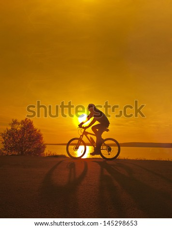 silhouette of a cyclist at orange sunset with reflection on water Space for inscription