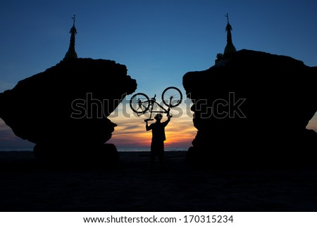 silhouette of a cyclist between two stupas on the background of sunset, Ngwe Saung Beach, Myanmar(Burma)  - stock photo