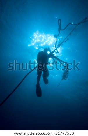 Silhouette of a diver ascending on a rope, backlit on a blue background. Sharm el Sheikh, Red Sea, Egypt. - stock photo