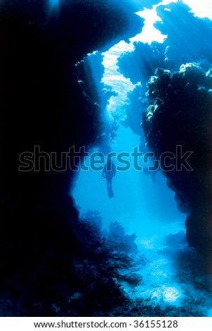 Silhouette of a diver with sun rays through a cave - stock photo