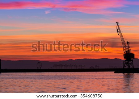 Silhouette of a drilling rig against dramatic sunset - stock photo