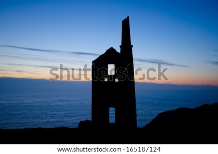 Silhouette of a engine house ruin on a cliff in front of the sea and sunset in Cornwall, UK - stock photo