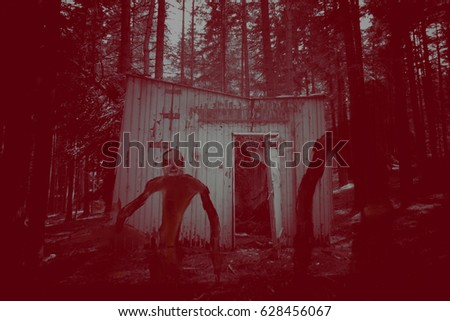 silhouette of a evil creature in front of abandoned ghostly house in the woods (symbolizing dark ghosts, horror or fear)