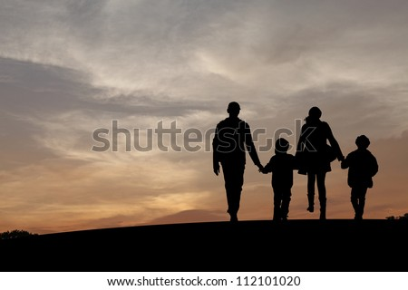 Silhouette of a family comprising a father, mother and two children walking into the sunset. - stock photo
