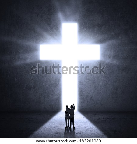 Silhouette of a family looking at the Cross of Jesus - stock photo