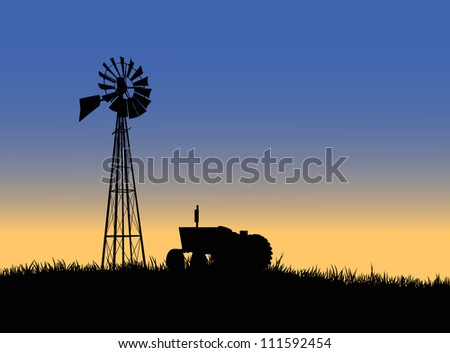 Silhouette of a farm tractor and windmill. - stock photo
