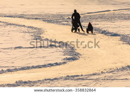 Silhouette of a father with children skating on ice during sunset in Holland - stock photo
