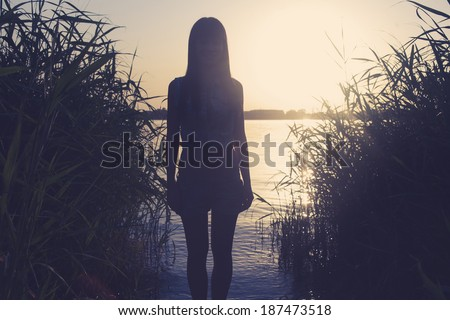Silhouette of a  female against water backlit shot yoned image - stock photo