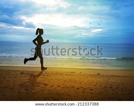 Silhouette of a female figure jogging at the beach
