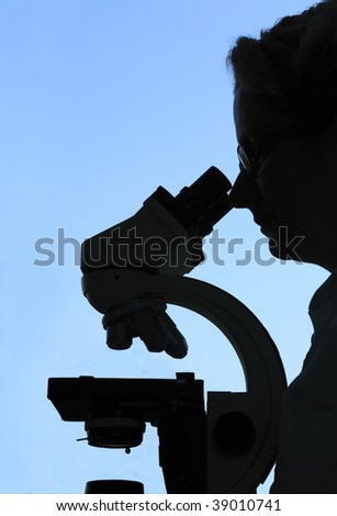 Silhouette of a female researcher looking through a microscope against a blue sky.