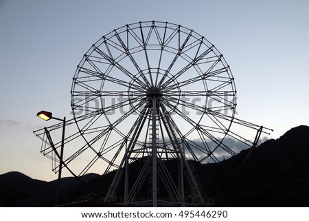 Silhouette of a Ferris wheel under construction at dusk