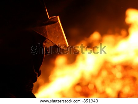 Silhouette of a firefighter facing a blazing fire - stock photo