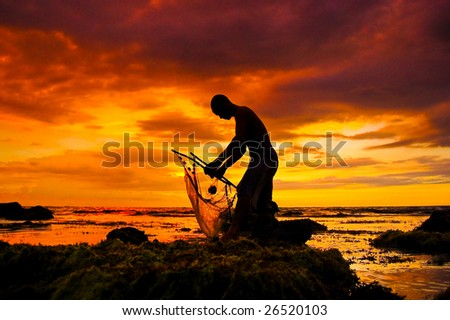 silhouette of a fisher with a fishing net at sunset - stock photo