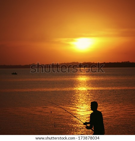 silhouette of a fisherman and his fishing rod during golden sunset