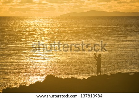 Silhouette of a fisherman at sunset - stock photo