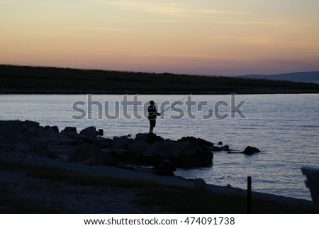 Silhouette of a fisherman in the sunset, standing at the rocky coast of the mediterranean sea at Vir Peninsula, Croatia; 14/06/2012