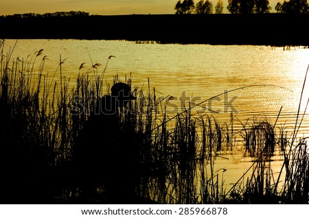 silhouette of a fisherman on the river at dusk - stock photo