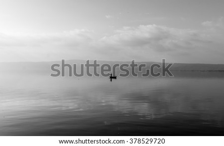 Silhouette of a fisherman's boat at lake - stock photo